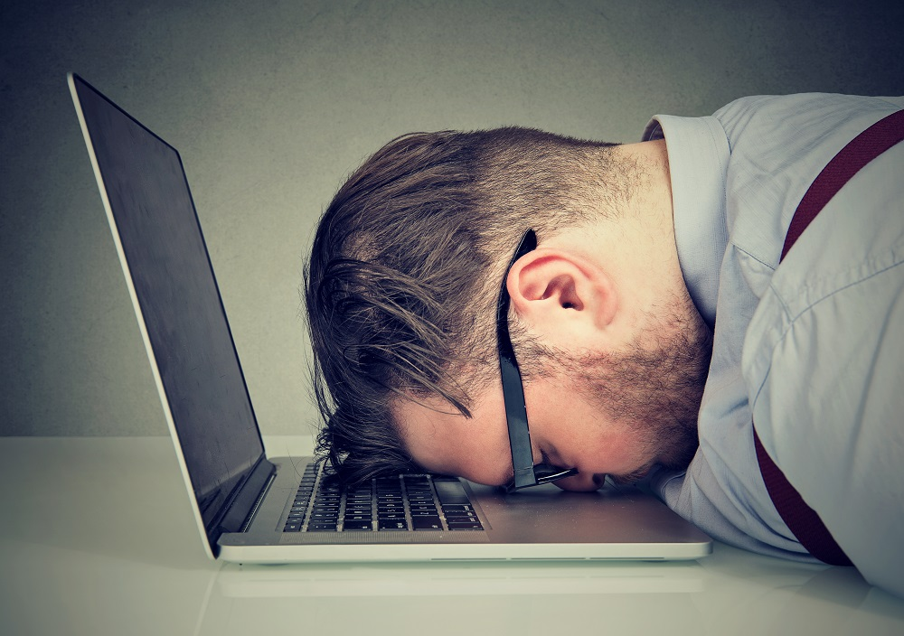 Frustrated man with head on laptop